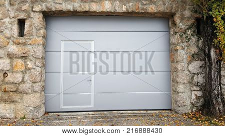 Modern roll up metal garage doors with integrated smaller doors inside traditional stone wall frame with two openings, large old tree and small rusted metal ring on the side