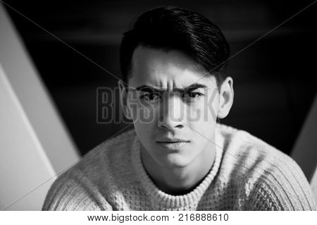 A young man with dark hair and eyes frowns. Reverie