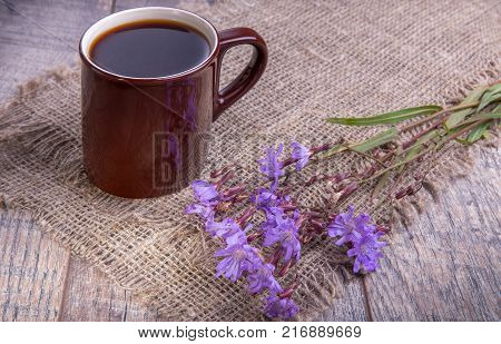Medicinal plant chicory: flowers. The roots of the plants are used as a substitute for coffee. Drink from chicory in a cup on the old wooden table. Rustic style, selective focus.