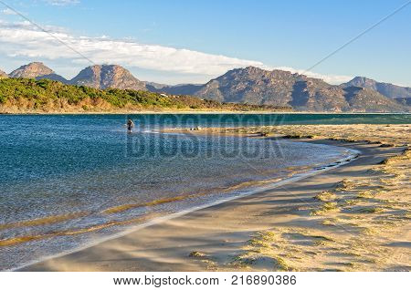 An angler in the shallow water on the Nine Mile Beach near Swansea with the Freycinet National Park in the distance - Tasmania, Australia