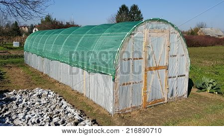 Plastic greenhouse with wooden doors, thick green net on top situated in garden surrounded with plants and uncut grass with houses and blue sky in background