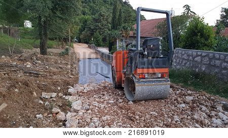 Road reconstruction with new layer of nylon and stone foundation, preparation for asphalting, and flattening everything with road roller