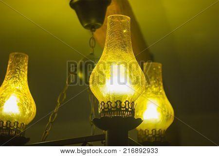 Old antique kerosene oil lantern brass hurricane lamp with hot burning flame casting light in a vintage glass chimney