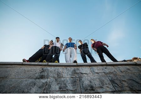 From below group of parkour professionals standing and posing on the wall.