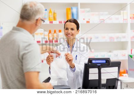 medicine, pharmaceutics, health care and people concept - female apothecary giving senior male customer his purchase in bag at drugstore