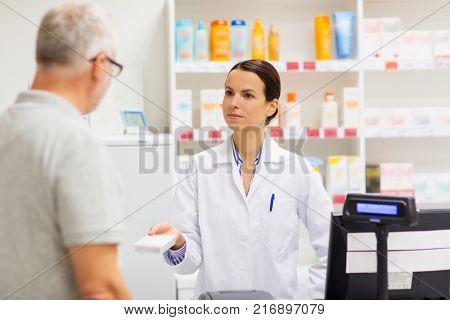 medicine, pharmaceutics, health care and people concept - apothecary giving drug to senior man customer at drugstore