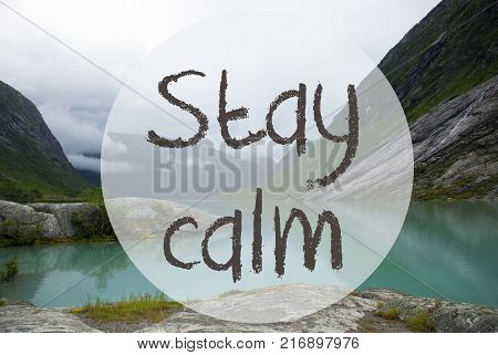 English Text Stay Calm. Lake With Mountains In Norway. Cloudy Sky. Peaceful Scenery, Landscape With Rocks And Grass. Greeting Card