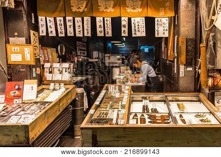 Nishiki Market, Kyoto - October 22, 2016: A fishmonger store selling varieties of fish which are cooked in many ways. A customer is gazing around inside the store as his order is being neatly wrapped.