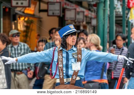 'Gion' district, Kyoto, Japan - October 23, 2016: Between 'Hanamikoji Dori' and 'Shijo Dori' junction, a female traffic warden extends her arms to stop crowd wanting to cross the street while letting cars going through.