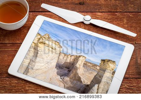 reviewing aeiail image of Monument Rocks in western Kansas prairie on a digital tablet with a cup of tea