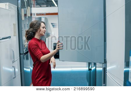 Smart modern female customer choosing large fridges in domestic appliances section. She looks happy