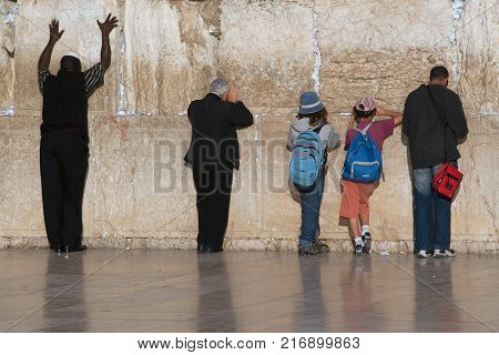 Men and boys are Jews near the great sacred Wailing Wall in Jerusalem, Israel.
