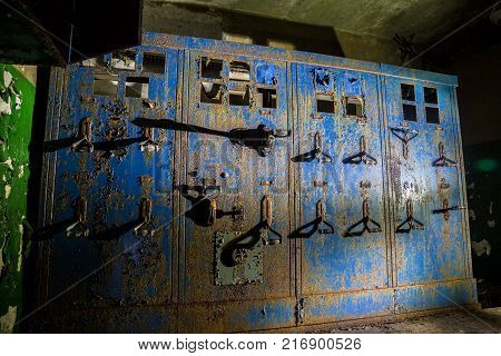 Old rusty electrical switchboard in abandoned factory or bunker.