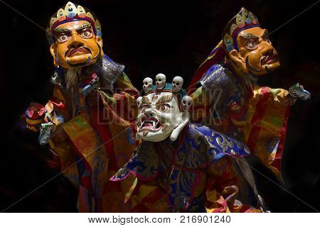 Three Buddhist manahs in ancient ritual robes perform the performance of the Lama's Dance in Masks, the White Mask of Mahakala and the two yellow Masks of Zambal.
