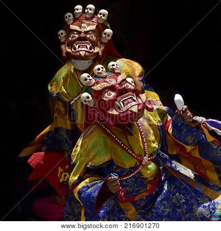 Buddhist monks in the ancient Red Mahakala Masks with skulls on the top of the mask perform ritual Cham Dance, Zanskar, Northern India.
