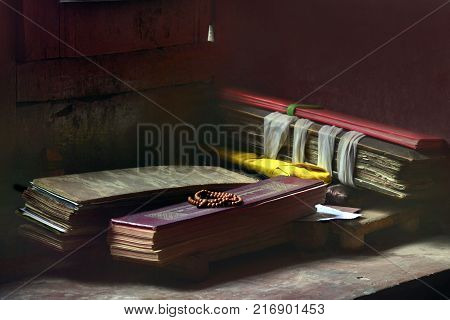Tibetan prayer sacred books, tied with yellow ribbons, lie next to a maroon stone wall.