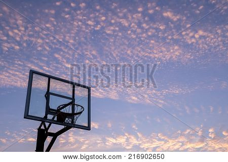Silhouette of outdoor basketball goal with clear backboard and sunset in the background visible through backboard