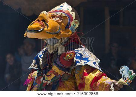Tibetan monk in ritual bright clothes Yellow Mahakala performs the Cham Dance in the monastery of Zanskar, Northern India.