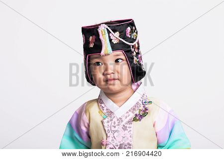 A studio portrait of a young girl wearing a Korean traditional costume, Hanbok, with a happy smile