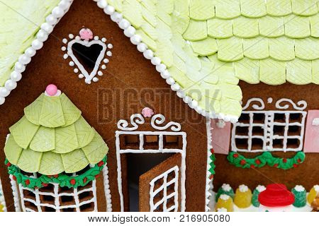 Festive Christmas gingerbread house with white decorative frosting and green roof shingles icing.