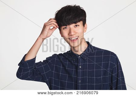 A studio portrait of an Asian young man making a happy smile