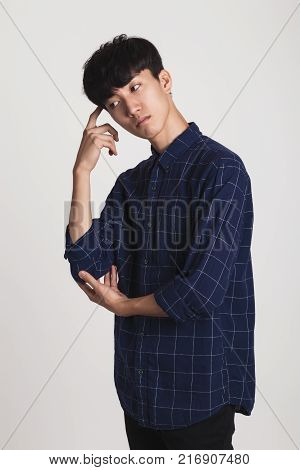 A studio portrait of an Asian young man who is troubled and deep in thought