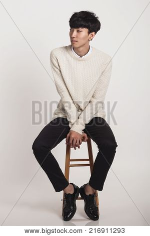 Full body portrait of an Asian man sitting on a chair and reminiscing about something faintly