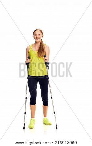 Portrait of happy young woman practising nordic walking