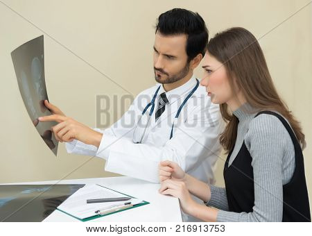Doctor having conversation with his patient and explaining skeleton xray result to patient in medical office