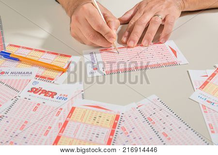Istanbul, Turkey - October 07, 2017. Hand marking number on Turkish  lottery ticket with pencil.