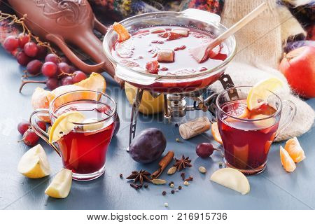 Winter alcoholic drinks - mulled wine, punch, grog. Glass jars with mulled wine. Hot fruit tea. Spices, fruit. Hot wine