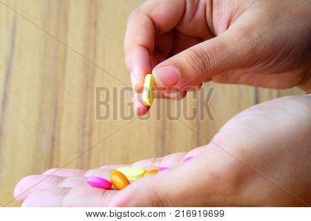 Women's hand hold medicine, boxes of medicines in the backgroundWomen's hand hold medicine, boxes of medicines in the background