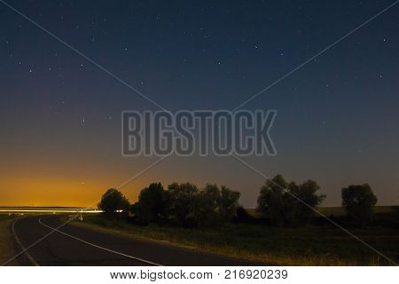 Highway in the field under the night sky with the stars