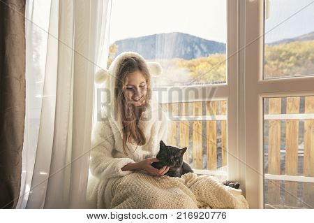 Portrait of teenage girl relaxing with her pet cat by the window