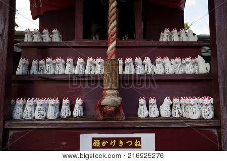 Nagano - Japan,June 3, 2017: Row of small votive Kitsune, fox figurines, animal guardians in front of an Inari Shrine