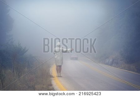 Young female in a raincoat on the road in the fog. Travel of women in the raincoat hitchhiking in the rain