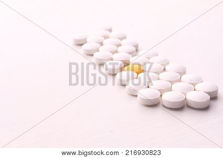 Round pills on White Background. a yellow pills on middle
