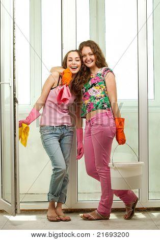 ?heerful girls washing the window with mop
