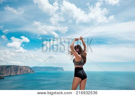 Beautiful sexy slender girl on top of a mountain overlooking the sea in a bikini, doing sports and fitness, listening to music on headphones
