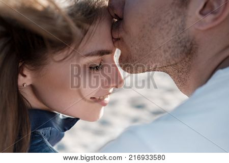 Beautiful couple, man and girl kissing and hugging on a sandy beach by the sea at sunset in sun glasses