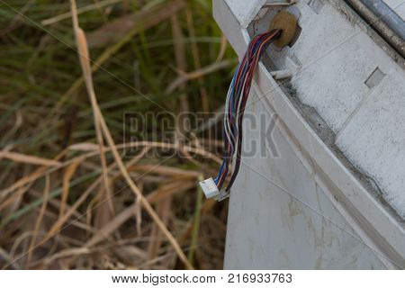 Bundle of wires with white connectors hanging from dirty white appliance discarded on side of road