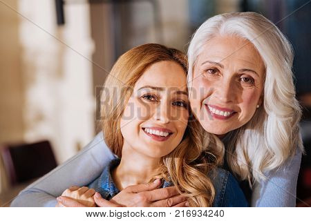 Close people. Positive cheerful young woman feeling happy while meeting and hugging her kind granny
