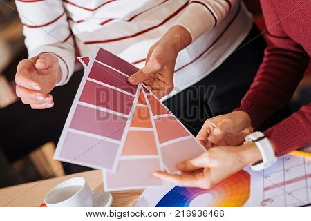 Color palette. Creative enthusiastic designers choosing an appropriate color while holding three beautiful color palettes