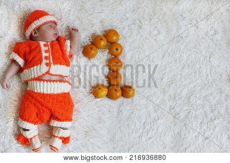 One month baby. Sleeping newborn baby one month old in orange knitted costume on white fur blanket with numeral one next to him and space for text. Greeting card or invitation.