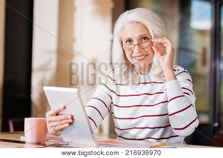 Progressive woman. Cheerful clever progressive elderly woman looking happy while sitting at the table and holding a new convenient gadget with her left hand touching the glasses