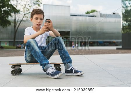 Summer day. Boy in white T-shirt and jeans sitting outdoor on longboard and uses smartphone. Boy plays computer games on digital gadget, surfing internet. Social networks, computer games.