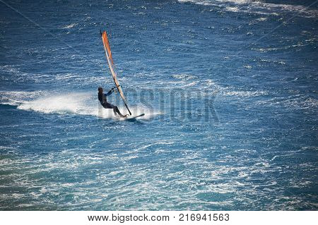 One windsurfing sail on the blue sea at windy day