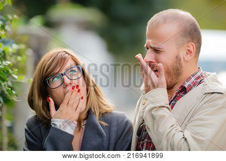 Bored urban couple yawning on the street.
