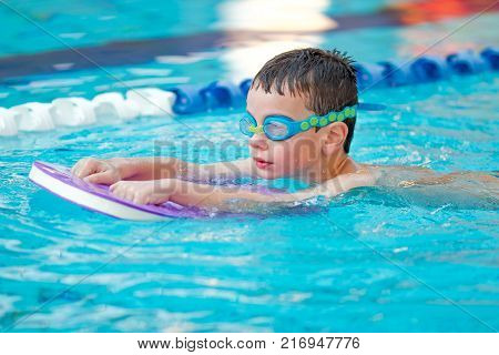 child is practicing swim in pool with googles