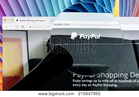 Sankt-Petersburg Russia December 5 2017: Paypal website homepage on a Apple iMac monitor screen under magnifying glass. PayPal is an international e-commerce business allowing payments and money transfers.